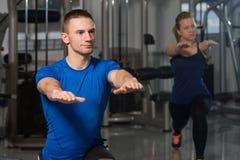 Les gens s'étirant pendant la classe de forme physique au centre de fitness Image stock