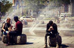 Les gens s'asseyant à la fontaine de Karlsplatz à Munich Image libre de droits