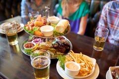Les gens s'asseyant à la table avec la nourriture et la bière à la barre Photo stock