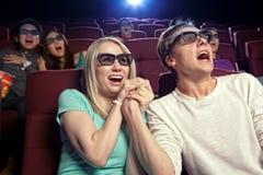Les gens s'asseyant au cinéma, observant un film Photos stock