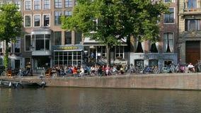 Les gens s'asseyant au soleil à un canal à Amsterdam, Pays-Bas banque de vidéos