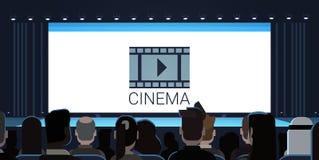 Les gens s'asseyant dans le cinéma regardant la vue arrière de attente de début de film d'écran vide de retour Photos libres de droits