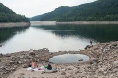 Les gens s'asseyant dans le costume nagent dans le lac de frontière Photographie stock libre de droits