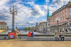 Les gens s'asseyant et détendent sur le pont de la rivière Limmat, Zurich, Image libre de droits