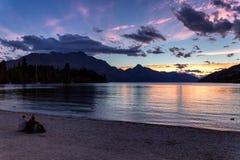 Les gens s'asseyant par le lac Wakatipu et beau coucher du soleil de observation à Queenstown photo libre de droits