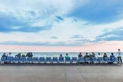 Les gens s'asseyant sur des chaises à la côte dans gentil image libre de droits