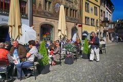 Les gens s'asseyant sur des restaurants au vieux village, chope en grès AM Rhei Photos libres de droits