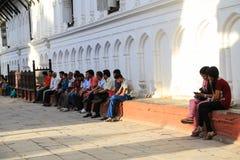 Les gens s'asseyant sur l'étape dans la place durbar de Katmandou images stock