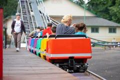 Les gens s'asseyant sur l'amusement montent en parc de chênes image libre de droits
