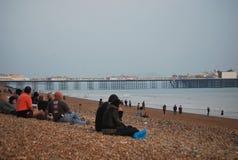 Les gens s'asseyant sur la plage à Brighton, R-U Image libre de droits