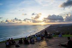 Les gens s'asseyant sur la terre et la montre pour l'ensemble du soleil photos stock