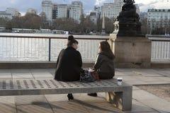 Les gens s'asseyant sur le banc sur la banque du sud du ` s de Londres donnant sur Riv Image stock
