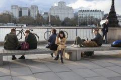 Les gens s'asseyant sur le banc sur la banque du sud du ` s de Londres donnant sur Riv Photo stock
