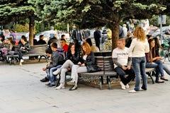 Les gens s'asseyant sur un banc de parc dans Bitola Image stock
