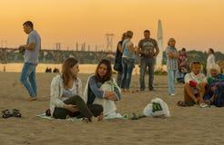 Les gens s'asseyant sur une plage de rivière de Dniepr Images stock