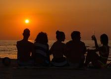 Les gens s'asseyant sur une plage regardant le coucher du soleil Image stock