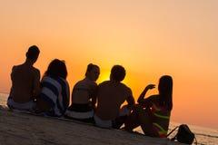Les gens s'asseyant sur une plage regardant le coucher du soleil Photographie stock