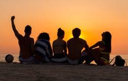 Les gens s'asseyant sur une plage regardant le coucher du soleil Images stock