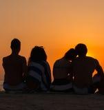 Les gens s'asseyant sur une plage regardant le coucher du soleil Photos libres de droits