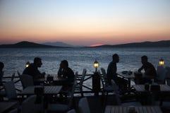 Les gens s'asseyent dans le restaurant de bord de la mer au crépuscule Photographie stock libre de droits