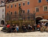 Les gens s'asseyent par une fontaine et lisent ou parlent avec des amis Photos stock