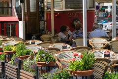 Les gens s'asseyent sur le restaurant de balcon un jour ensoleillé, bl abstrait photographie stock libre de droits