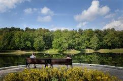 Les gens s'asseyent sur un banc et regardent l'étang Image libre de droits