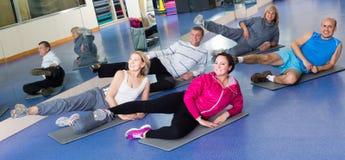 Les gens s'exerçant dans un gymnase sur des tapis de sport Image stock