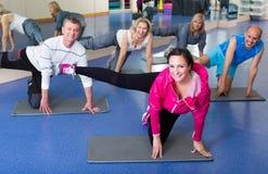 Les gens s'exerçant dans un gymnase sur des tapis de sport Photographie stock
