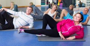 Les gens s'exerçant dans un gymnase sur des tapis de sport Photos libres de droits