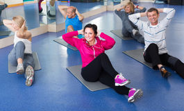 Les gens s'exerçant dans un gymnase sur des tapis de sport Image libre de droits