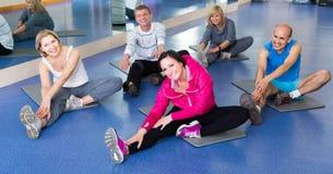 Les gens s'exerçant dans un gymnase sur des tapis de sport Photo stock