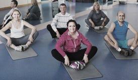 Les gens s'exerçant dans un gymnase sur des tapis de sport Images libres de droits