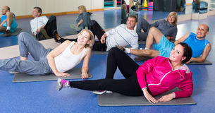Les gens s'exerçant dans un gymnase sur des tapis de sport Images stock