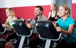 Les gens s'exerçant sur des vélos d'exercice ensemble Images stock