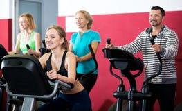 Les gens s'exerçant sur des vélos d'exercice ensemble Photographie stock libre de droits