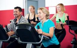Les gens s'exerçant sur des vélos d'exercice ensemble Image stock