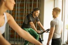 Les gens s'exercent sur les vélos stationnaires dans la classe de forme physique Images libres de droits