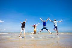 Les gens sautant à la plage Photographie stock libre de droits