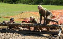 Les gens sautant au-dessus des identifiez-vous boueux la boue tout en concurrençant dans une course de boue Images stock
