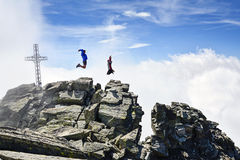 Les gens sautant sur les montagnes Photographie stock libre de droits