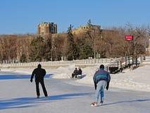 Les gens scating et détendant sur un banc sur le canal congelé de rideau à Ottawa image libre de droits