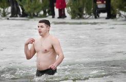 Les gens se baignent en rivière en hiver. Épiphanie chrétienne de festival religieux Photos stock