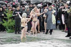 Les gens se baignent en rivière en hiver. Épiphanie chrétienne de festival religieux Images stock