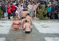 Les gens se baignent en rivière en hiver. Épiphanie chrétienne de festival religieux Photographie stock