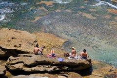 Les gens se bronzant sur une roche Images stock