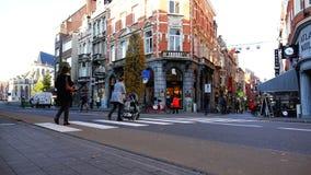 Les gens se déplacent le long et à travers de la rue habillée dans des vêtements de demi-saison clips vidéos