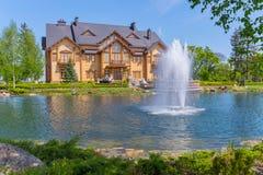 Les gens se reposant près d'une maison sur la banque verte d'un étang avec une fontaine Photo stock