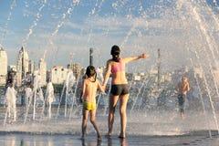 Les gens se sauvant de la chaleur dans une fontaine de ville au centre d'une ville européenne Photo libre de droits