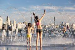 Les gens se sauvant de la chaleur dans une fontaine de ville au centre d'une ville européenne Image libre de droits